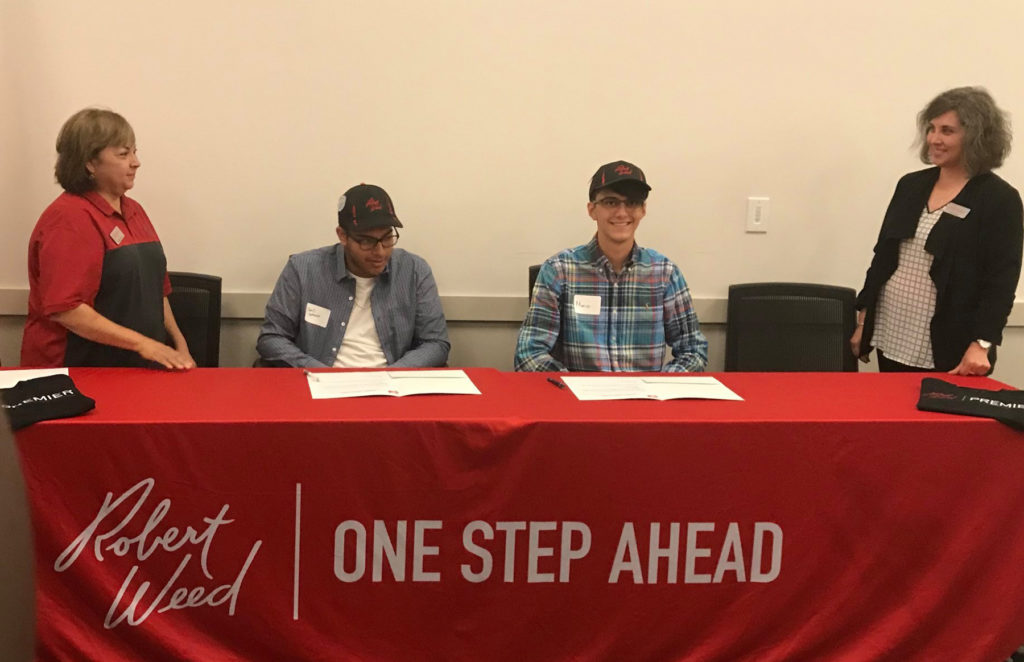Mario Garcia (right, sitting) signs his letter of intent to become a youth apprentice at Robert Weed Corporation in Elkhart in 2019.